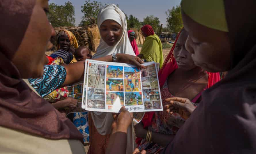 People look at educational material about mine dangers in a village near Maiduguri