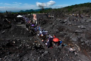 Relatives and friends of the victims of the Fuego volcano eruption march a year after the disaster in San Miguel Los Lotes, Guatemala