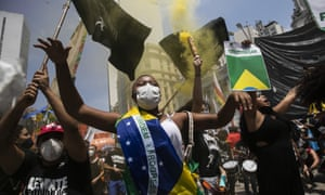 A woman, wrapped in a Brazilian national flag, chats slogans during a protest against Brazilian President Jair Bolsonaro calling for his impeachment over his government's handling of the pandemic and accusations of corruption in the purchases of vaccines in Rio de Janeiro.