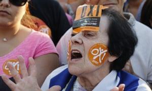 A demonstrator wears 'oxi' (no) stickers during an anti-austerity rally in Athens.