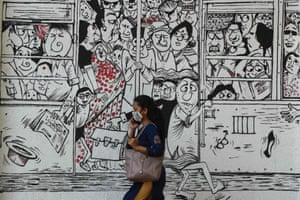 Mumbai, India. A pedestrian passes a mural depicting people travelling on overcrowded public transport, to raise awareness about social distancing measures and the use of masks