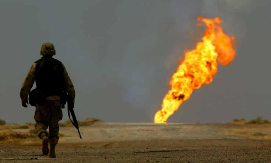 US ARMY SOLDIER WALKS TOWARDS BURNING OIL WELL IN SOUTHERN IRAQA U.S. Army soldier walks towards a burning oil well in Iraq's vast southern Rumaila oilfields March 30, 2003. U.S. engineers moved through the oilfields on Sunday shutting down wellheads in an operation that could take months to complete. Having discovered a cache of arms and a minefield, U.S. troops must tread carefully in their mission to safeguard the region's oilfields, which pumped more than half of Iraq oil exports before the war began. REUTERS/Yannis Behrakis