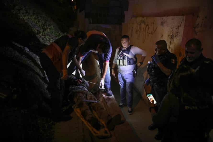 Red Cross first responders treat 30-year-old Jesús Bernal after he was found with at least four separate gunshot wounds in his legs and wrists
