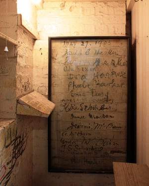Part of the brick wall has been carefully framed to preserve artists' signatures.