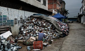 A man sorts through electronic waste at a scrapyard in Guiyu, China