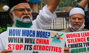 Protesters in Mumbai hold placards during a protest against the Chinese government's policies on Uighur people.