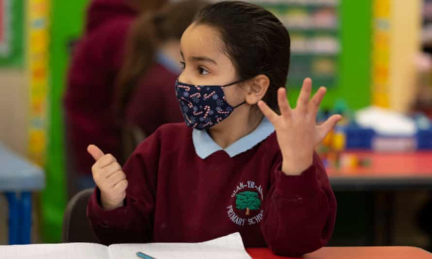 A child wearing a face mask counts during a maths lesson.