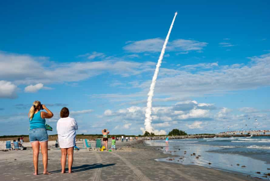 Watching a rocket launch from Cape Canaveral on Cocoa Beach, just to the south of the launch site, Florida,