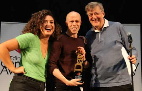 Brookes receives his trophy at the Dave's Edinburgh Comedy awards from 1981 winner Stephen Fry and 2018 best comedy show winner Rose Matafeo.