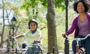 A woman and child cycling through a park