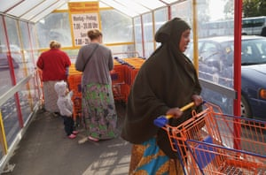 Somali refugee Efrah Abdullahi Ahmed, right, along with refugees from Chechnya, shopping for groceries