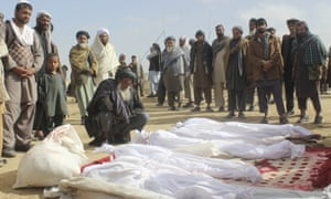 In a November photo, Afghan villagers gather around the bodies of several people who were killed during clashes between Taliban and Afghan security forces in Buz-e Kandahari village in Kunduz province, Afghanistan.
