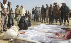 Villagers gather around the bodies of civilians killed in clashes between Taliban and Afghan security forces in Kunduz province.