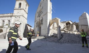 Firefighters walk past Norcia's damaged town hall and basilica the day after the earthquake hit central Italy, on 31 October 2016.