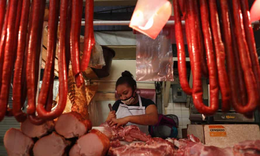 A butcher wears a mask as she works inside a public market in Mexico City.