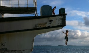 Children jump off a wrecked ship that was a victim of a cyclone that hit the small South Pacific island nation of Tuvalu, which is striving to mitigate the effects of climate change. Rising sea levels of 5mm per year since 1993, well above the global average, are damaging vital crops and causing flooding in the low-lying nation at high tides