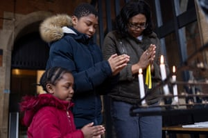 Opel Connolly with her two children, Angel and Sean light a candle of remembrance during a small service at St Catherine's Church in London