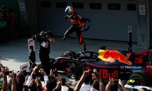 Daniel Ricciardo celebrates victory by leaping off his car.
