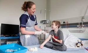 Clare Pheasant treats Finlay, 7, on Rose ward.
