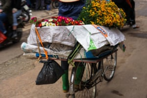 Close-up image of a bicycle in Hanoi, Vietnam, laden with flowers for sale.