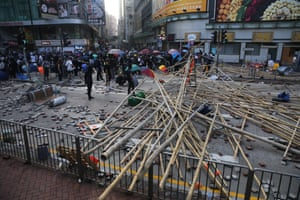 Protesters gather in a street strewn with bamboo poles and bricks during clashes outside the university