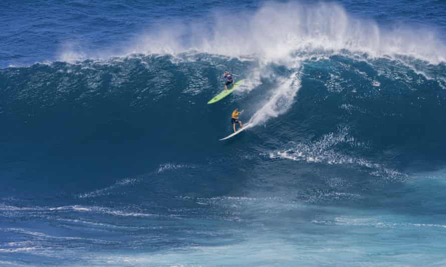 Laura Enever, upper left, and Felicity Palmateer, both of Australia, ride a wave at a Maui surf break known as Jaws.