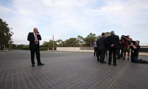 Crossbench senator David Leyonhjelm talks on his phone while his colleagues, senators Bob Day, Ricky Muir and John Madigan have their photograph taken outside Parliament House on Tuesday.