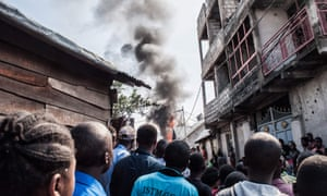 Residents look on as smoke rises after the plane crash in Goma, Democratic Republic of Congo
