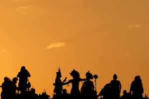 Indigenous people silhouetted against twilit sky