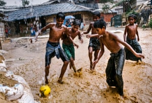 Children enjoy a game of football in monsoon rains, in Cox's Bazar, October 2017
