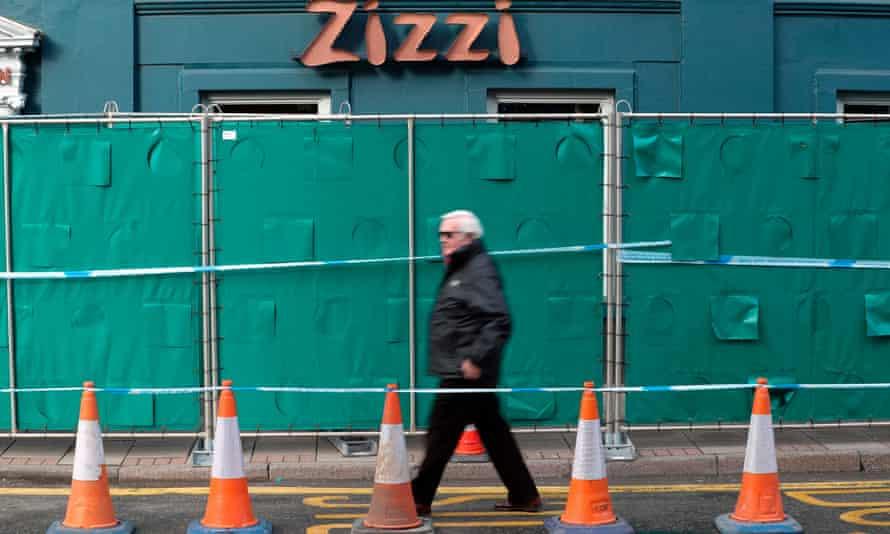 Man walks past green barricade in front of Zizzi restaurant in Salisbury