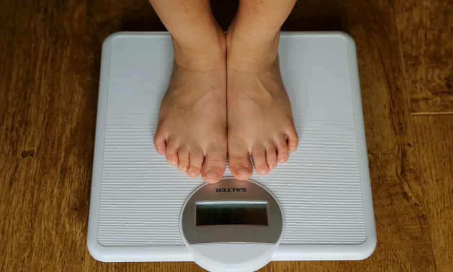 Person standing on bathroom scales.