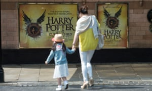 A woman and child head towards a theatre showing Harry Potter and the Cursed Child