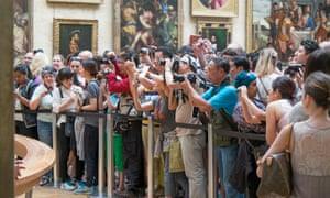 Tourists photographing the Mona Lisa at the Louvre in Paris