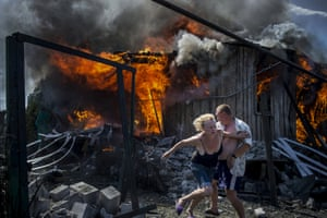 Long-term projects – first prize Residents escape from a fire at a house destroyed by an air attack in the village of Luhanskaya, Ukraine