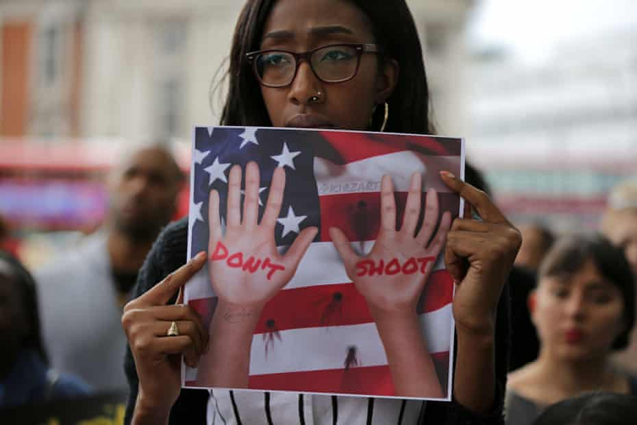 A women holds up a placard to protest against police brutality.