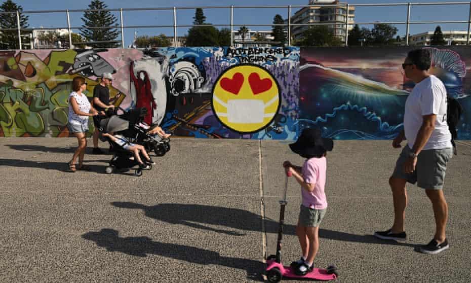 People look at a Covid-inspired mural at Bondi beach