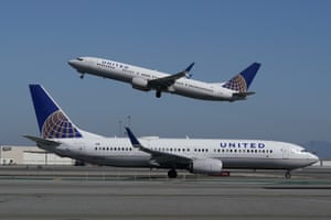 A United Airlines airplane takes off over a plane on the runway at San Francisco International Airport in San Francisco.