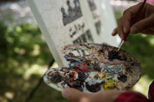 Meher Aqa Sultani, 26, works on a painting in Artlords' garden in Kabul.