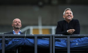 Alan Shearer and Gary Lineker watch from the stands.