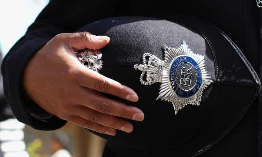 Metropolitan police officer holding their hat.