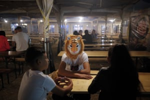 Children, one wearing a tiger mask, sit at a table in the food area at the funfair in Titu