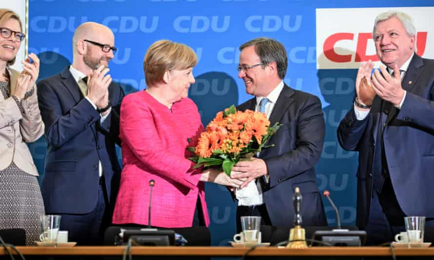 Armin Laschet (second right), regional leader of the Christian Democratic Union in North Rhine-Westphalia, receives flowers from German chancellor and party chair Angela Merkel.