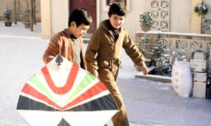 Two boys, Ahmad Khan Mahmoodzada and Zekeria Ebrahimi, walking along a street, looking happy and lively, one holding a kite, in The Kite Runner (2007)