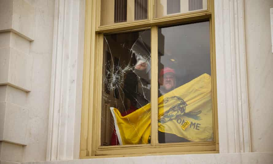 A member of a pro-Trump mob shatters a window inside the Capitol after breaking into the building.