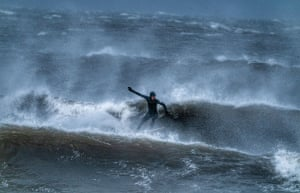 Tynemouth, UKA surfer braves stormy seas off the North East coast