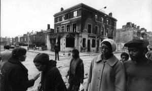 Brixton residents walking amid the debris left by rioting