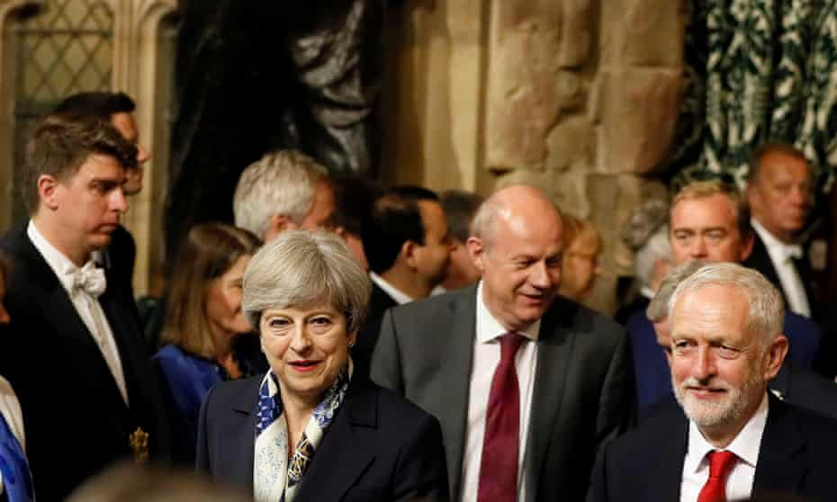 Theresa May and Jeremy Corbyn, walk through the Peers Lobby in the Houses of Parliament during the State Opening of Parliament