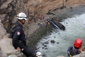 Rescue workers stand at the scene after a bus collided with a truck and fell down a cliff along a sharply curving highway north of Lima.