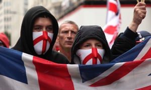 Masked English nationalists march carrying a union flag